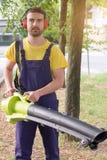 Gardener using his leaves blower in the garden stock photography