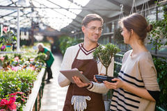 Free Gardener Using Tablet And Talking With Woman Holding Bonsai Tree Royalty Free Stock Images - 65287189