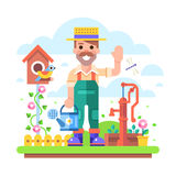 Gardener with watering can stands near water pump. Royalty Free Stock Image