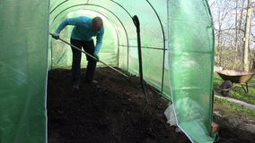 Gardener work hard with soil in new greenhouse. stock video footage