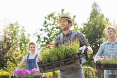 Gardeners carrying flower pots in crates at garden Stock Photo