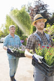 Gardeners carrying flower pots in crates at plant nursery Stock Photos