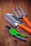 Gardeners hand tools - fork trowel secateur on wooden boards Stock Photography