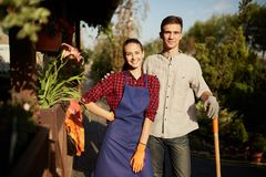 Gardeners nice girl in the apron and guy with a shovel stands in the wonderful garden on a sunny day stock image