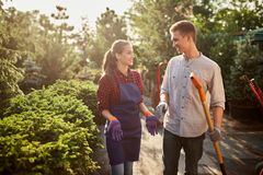 Gardeners nice girl in the apron and guy with a shovel walking on the garden path in the wonderful garden on a sunny day stock images