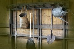 Garden tools hanging up in a garden shed. Gardeners tools in a row, hanging up against a bamboo background royalty free stock photo