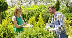 Gardeners working with papers. Young gardener woman standing and writing in documents while man doing horticulture job in the garden stock video