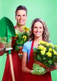 Gardening. Young couple with flowers. Over green background Stock Image
