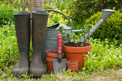 Gardening. Rubber boots, watering can and pots in a garden Stock Photo