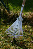 Gardening. Rake leaning against the garden fence stock image