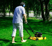 Gardening. A man pushing a lawn mower Royalty Free Stock Images