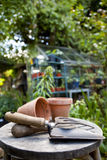 Gardening. Utensils and flowere pots resting on a stool in a green garden with a greenhouse out of focus in the background Royalty Free Stock Photography