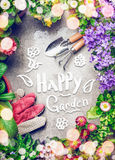 Gardening background with assortment of colorful garden flowers in pots , tools, and handwritten text happy garden Royalty Free Stock Image
