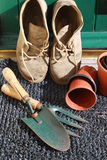 Gardening Boots. A pair of gardening boots resting against a green wooden back door with terracotta coloured pots and gardening tools surrounding Royalty Free Stock Photo