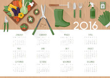 Gardening calendar 2016. With work tools, flower pots and vegetables in a crate on a  wooden table, top view Royalty Free Stock Photography