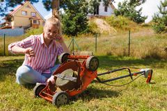 Person having problem with land mower stock image