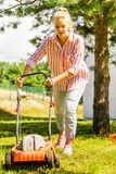 Gardening. Mowing lawn with lawnmower. Gardening. Female person mowing green lawn with lawnmower in sunny day royalty free stock photography