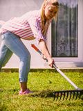 Woman using rake to clean up garden Royalty Free Stock Image