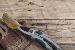 Gardening gloves with secateurs. Gloves and gardening secateurs on a wooden bench Royalty Free Stock Image