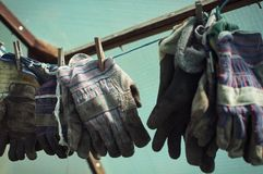 Gardening gloves. Side landscape view of gardening gloves, hanged up on a wire Royalty Free Stock Photo