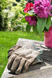 Gardening gloves on table. Cut flowers from the spring garden and a well-worn pair of gardening gloves Royalty Free Stock Images