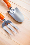 Gardening hand tools - trowel and fork on wooden boards Stock Photography