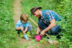 Gardening hobby. Dad teaching little son care plants. Spring gardening routine. Planting flowers. Little helper in. Garden. Farm family. Little boy and father royalty free stock images