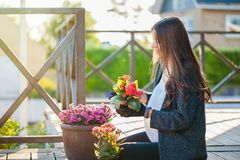 Gardening hobby and leisure concept. Young woman sitting and smiling, gardening in pots on the terrace, at home. Gardening as hobby and leisure concept stock photography