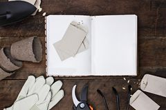 Garden Journal and Planting Seeds. Gardening journal surrounded with tools, tomato seeds and flower pots on a rustic wooden table. Image shot from above in flat Royalty Free Stock Photography