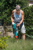 Gardening 3. Man busy and concentrated trimming grass in the garden Stock Image