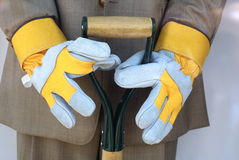 Gardening on the Run. Male mannequin holding shovel in business suit with garden gloves royalty free stock photos