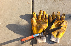 Gardening scissors and dirty yellow gloves Stock Photography
