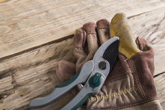Gardening secateurs with gloves. Gloves and secateurs on a bench Royalty Free Stock Photography