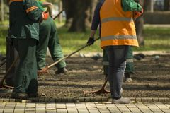 Gardening service workers preparing ground in park with garden tools royalty free stock photo
