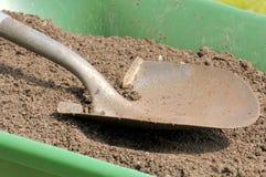Gardening-Shovel-Soil. A shovel rests on sandy topsoil in a wheelbarrow. Focus = dirt near footstep. 12MP camera Royalty Free Stock Photo