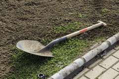Gardening spade on grass and compost, ready to the spring season Royalty Free Stock Images