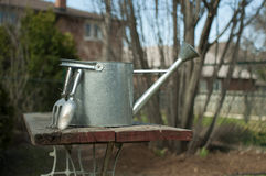 Gardening Still Life with a Watering Can. Watering can and tools on an aged wooden table Stock Photos