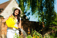 Gardening in summer - woman watering flowers Stock Photo
