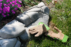 Gardening time. A pair of gardening gloves left by the side of a flower garden, with a border of stones Stock Images