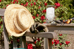 Gardening tools. Hat, gardening gloves and tools with cool glass of ice water Royalty Free Stock Images