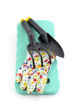 Gardening tools. Kneeling pad, gloves and hand gardening tools on white background in vertical format Stock Photo