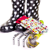 Gardening Tools. Gloves and rubber boots ready for some garden work. Focus on the tools Royalty Free Stock Photo