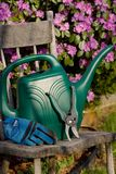 Gardening Tools. Watering can, shears, and gardening gloves on an old wooden kitchen chair, floral background Stock Photography