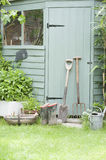 Gardening Tools Against Door Of Shed. Gardening tools lean against door of potting shed Royalty Free Stock Photography