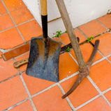 Gardening tools for the caribbean. A cutlass, shovel and pickaxe resting on red clay tiles Stock Photos