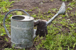 Gardening tools close up. Garden accessories - a watering can and gloves Royalty Free Stock Photography