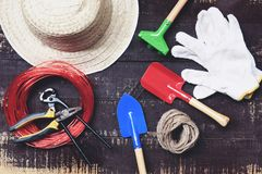 Gardening tools on dark wooden background with pliers , straw hat , rope , gloves trowel garden equipment. On top view stock images