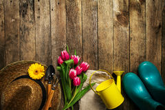 Gardening tools, flowers, watering can, rubber boots and straw h Stock Photography