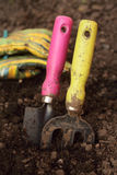 Gardening tools and gloves with dirt on the soil. Royalty Free Stock Photo