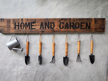 Gardening tools hang on the concrete wall Stock Photo